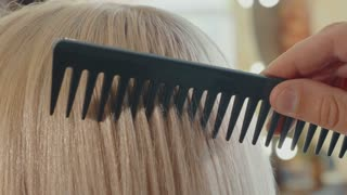 Male hairdresser combing hair to blonde girl in beauty salon, close-up