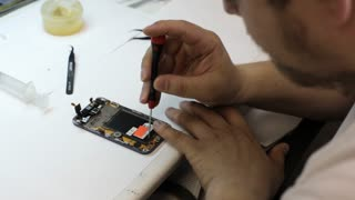 Male master disassembling smart phone for change broken details