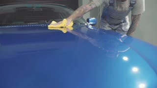 Master finish polish the deep blue sport car and wiping the hood by cloth