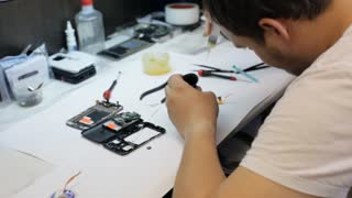 Master soldering microchip for mobile phone and using syringe with rosin.