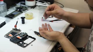Master takes out part for repair cell phone and preparing it for installation