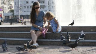 Mother and daughter feedings street pigeons in the park at summer day 4K slow