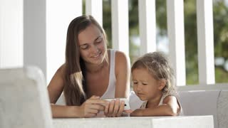 Mother and daughter watching funny video on smartphone at the balcony