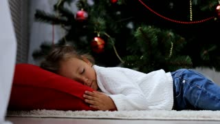 Mother comes and covers sleeps on floor baby with a red plaid at Christmas eve.