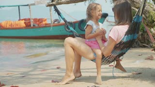 Mother having fun with her little cute daughter on hammock at the sandy beach