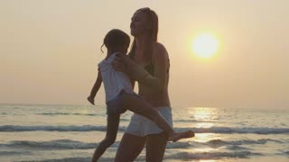 Mother spinning her little daughter at sandy beach in warm sunset light.