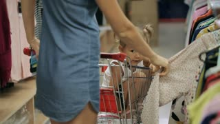 Mother with her little daughter selecting clothes at supermarket