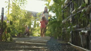 Mother with little girl walking on path in garden. Feet come near to camera.