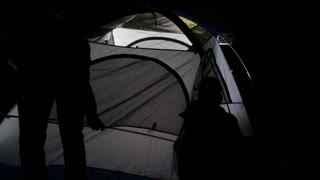 Night shot of two adult mans and child erecting tent in ligh from SUV.