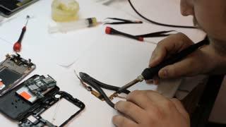 Repair master soldering details of mobile phone.