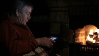 Senior man sits at the fireplace with tablet and watching family photos