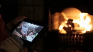 Senior man sits at the fireplace with tablet and watching family video