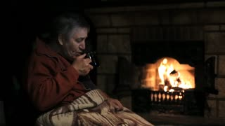 Senior man sitting at the fireplace and drinking a tea