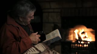 Senior man sitting at the fireplace with the book and drinking a tea