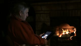 Senior man sitting by fireplace and using tablet