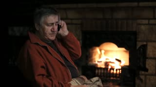 Senior man speaking by cell phone sitting in the chair in front of the fireplace