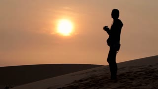 silhouette of lonely woman stand into desert and drink water at sunset