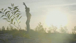 Silhouette of woman doing yoga exercises in a park at sunrise in slow motion