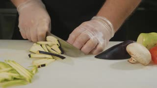 Slide slow motion of professional chef chopping vegetables, close-up