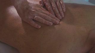 Spa therapist applying scrub on young woman back at luxury beauty salon.