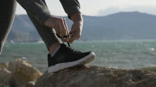 Sports woman getting ready for run tying laces of running shoes on the beach