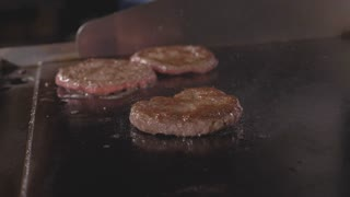 Street food restaurant, close-up grilling tree burgers cutlet on frying surface