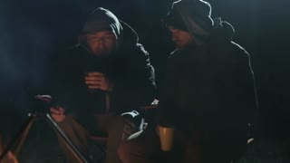Two friends sits next to bonfire in wood at night, talking and drinking tea.