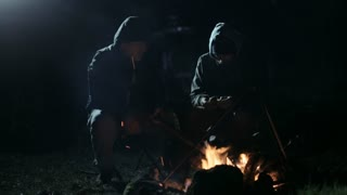 Two friends sitting at night next to bonfire fire and talking.