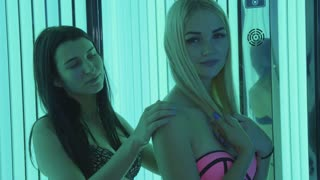 Two girlfriends in vertical solarium. Girl helps apply cream to her girlfriend.