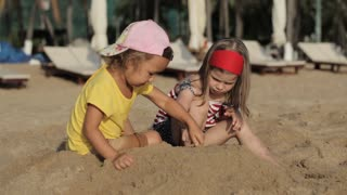 Two little cute girls playing with sand on the beach