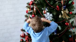 Two little kids brother and sister decorating Christmas tree at daytime