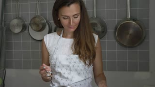 Woman adding ingredients to a bowl for cooking home made chocolate