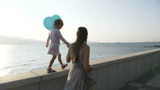 Woman goes by the hand with a little beautiful girl at morning in city seaside