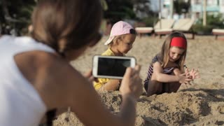 Woman shooting a video of two little cute girls playing with sand on the beach
