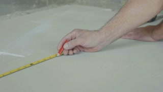 Worker marking a drywall sheet for installing it in newly built house.