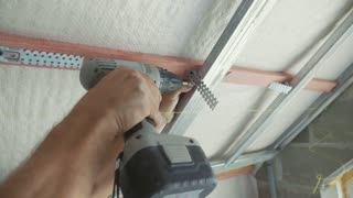 Worker mounting metal construction for drywall in a newly built house