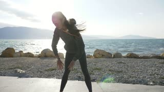 Young attractive woman warming up before running on the beach