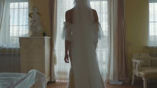 Young bride in wedding dress going from living room to balcony, slow motion
