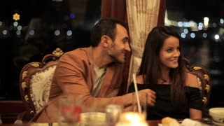 Young couple dining in a romantic atmosphere at restaurant on the boat