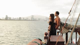 Young couple with wine glasses enjoys a sunset on the deck of cruise boat