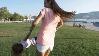 Young happy mother whirling her little cute daughter in sunny day at the park