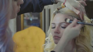 Young makeup artist applying concealer on model's face.