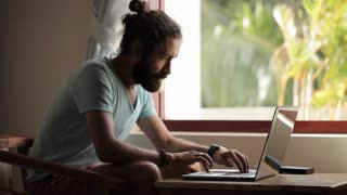 Young man finish working on laptop and lean back on chair