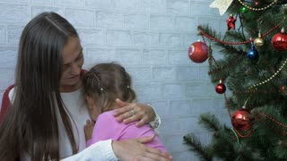 Young mother hugging her crying little daughter next to Christmas tree