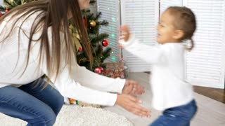 Young mother turns her little daughter with Christmas tree on the background. Mom and daughter having fun in xmas morning, slow motion 120fps