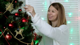 Young pretty woman decorating Christmas tree