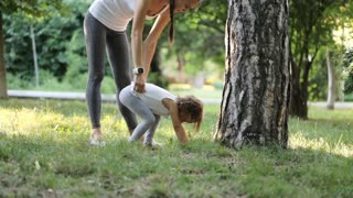 Young sporty mother coaching her little daughter in green summer park