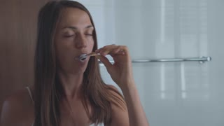Young woman brushing teeth with a tooth brush in bathroom