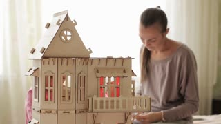 Young woman building dollhouse for her little daughter
