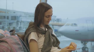 Young woman eats tangerine at airport with airplane on the background